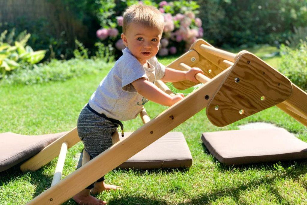 bambino gioca in giardino con il suo triangolo di pikler
