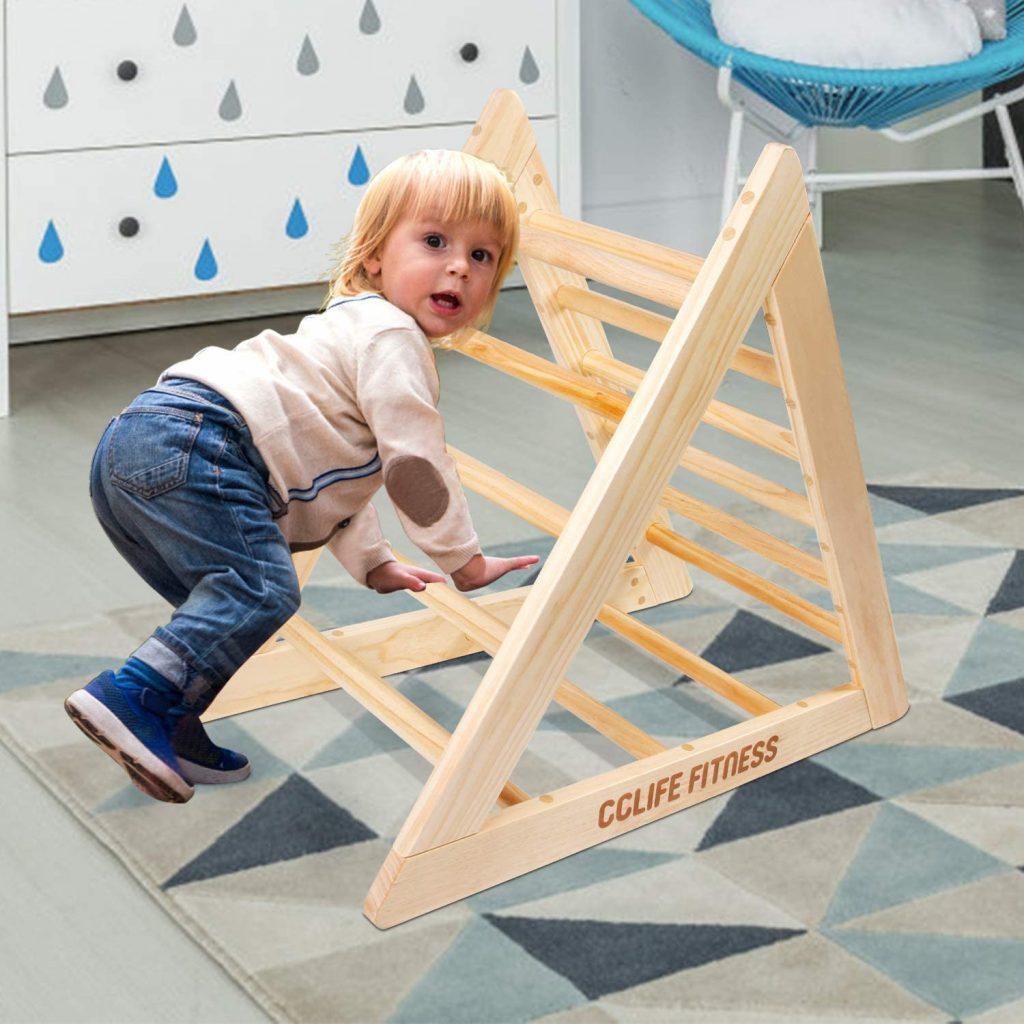 bambino gioca nel triangolo di pikler cclife